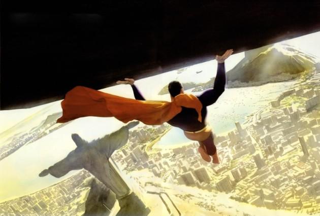 Superman em voo segurando um grande bloco. Abaixo dele é possível ver o Cristo Redentor no Rio de Janeiro
