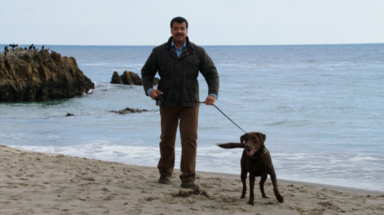 """COSMOS: A SPACETIME ODYSSEY: Host Neil deGrasse Tyson takes a dog for a walk at Drew Point, AK, to illustrate the difference between weather and climate in the all-new """"The World Set Free"""" episode of COSMOS: A SPACETIME ODYSSEY"""